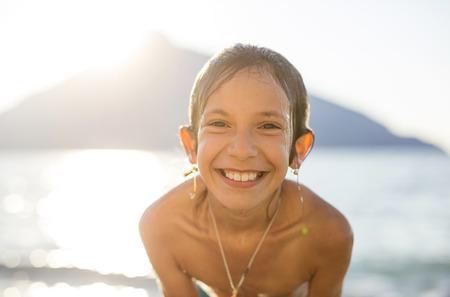 Retrato de niña feliz en la playa al atardecer