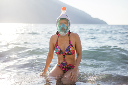 Caucasian young woman in mask for snorkling sitting in shallow water on beach 免版税图像