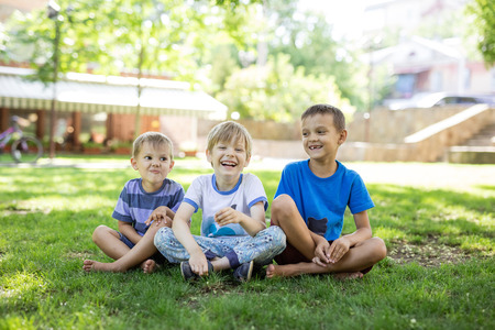 Three happy young boys in summer park. Friends or siblings sitting on green grass.