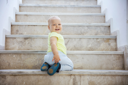Baby girl crawling up stairs outdoors, looking back and smiling