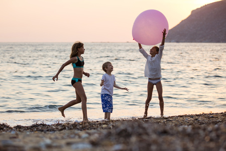 Three children playing with huge pink balloon on beach at sunset. Siblings on vacations at sea. Foto de archivo