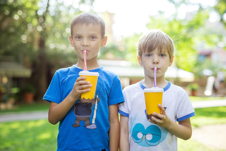 Two boys drinking cocoa from paper cups with straws in summer park