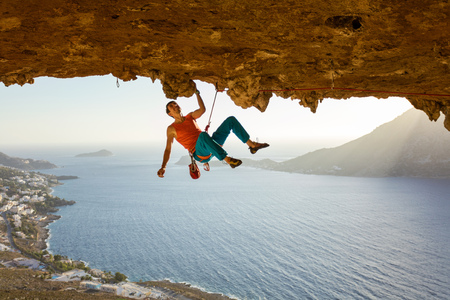 Male rock climber on challenging route going along ceiling in cave, view of coast below 스톡 콘텐츠