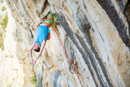 Male rock climber hanging upside down on challenging route, resting before keeping on his attempt