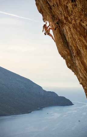 Young female rock climber on challenging route on overhanging cliff over sea