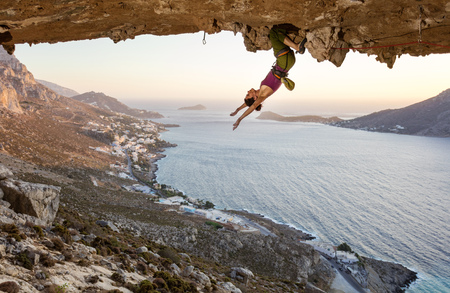 Female rock climber hanging upside down on challenging route in cave at sunset, resting before keeping on her attempt