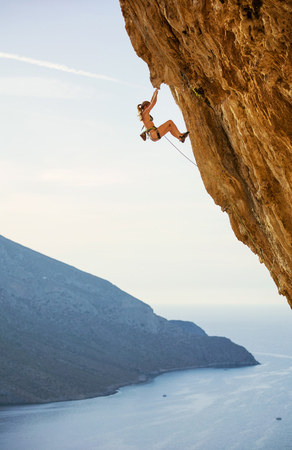 Caucasienne jeune femme en bikini escalade route difficile sur falaise en surplomb