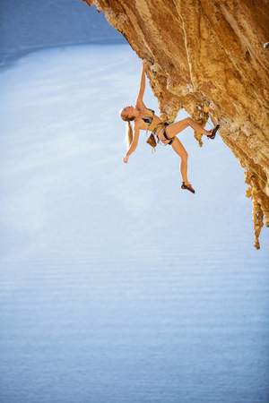 Young female rock climber in bikini hanging with one hand on overhanging cliff. On challenging climbing route over sea. 写真素材
