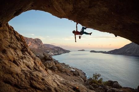 Hombre caucásico escalada desafiante ruta en la cueva, contra la hermosa vista del atardecer Foto de archivo
