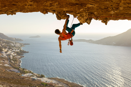 Male rock climber on challenging route going along ceiling in cave, Kalymnos, Greece 写真素材