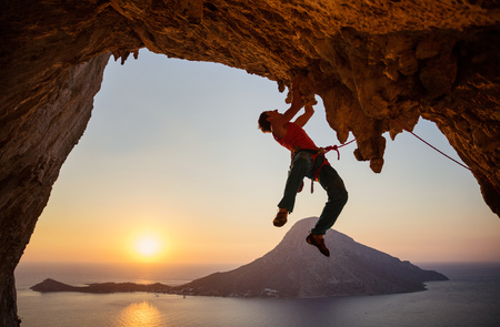 Grimpeur masculin sur une route difficile sur une falaise dans une grotte au coucher du soleil