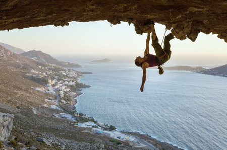 Young woman climbing in cave at sunset, Kalymnos Island, Greece Archivio Fotografico