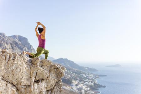 Młoda kobieta rasy kaukaskiej ćwiczy jogę lub ćwiczy stojąc na klifie na wybrzeżu morza