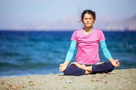 Caucasian young woman practicing yoga on beach, sitting in lotus position with closed eyes Banque d'images