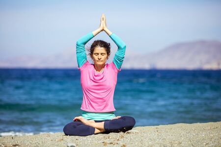 Caucasian young woman practicing yoga on beach, sitting with crossed legs and raised arms Stock Photo