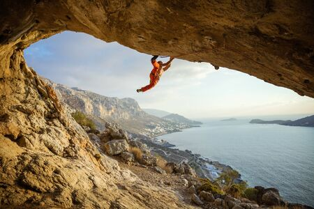 Young man climbing challenging route in cave against beautiful view of coast