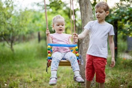 Young boy pushing toddler sister on swing. Siblings enjoying summer day in countryside. 版權商用圖片