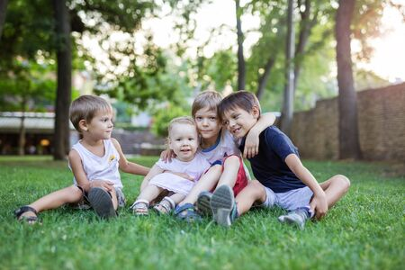 Three young boys and toddler girl in summer park. Friends or siblings sitting on green grass.
