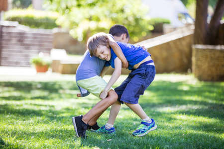 Two boys fighting outdoors. Siblings or friends wrestling in summer park. Siblings rivalry. Standard-Bild