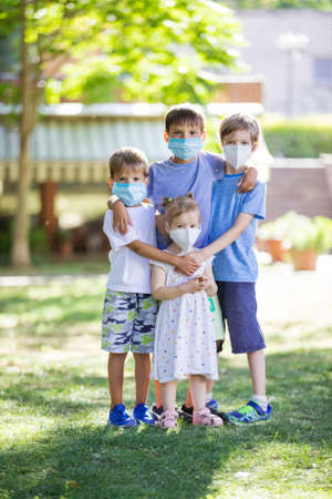 Young children in protective masks on faces outdoors. Quarantine. Kids wearing safety masks while posing in summer park. Coronavirus prevention.