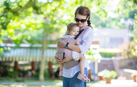 Caucasian woman and her daughter in baby carrier in summer park Standard-Bild