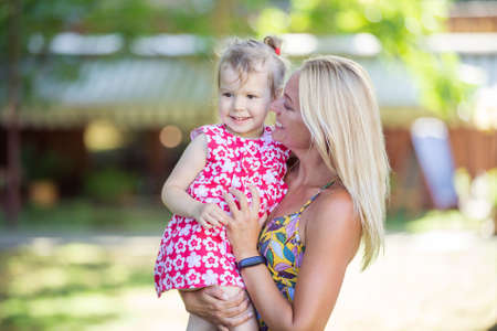 Beautiful young woman holding little girl in park, mother and daughter laughing and talking on walk in park