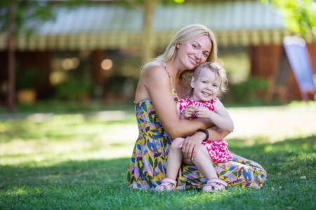 Mother and little girl in summer park. Woman is cuddling daughter, they are smiling and looking at camera.
