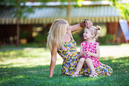 Mother and little girl in summer park. Woman is cuddling daughter, they are smiling and looking at one another with affection.