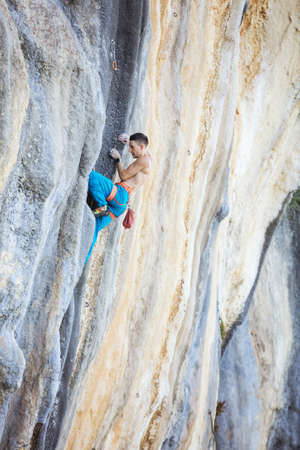 Caucasian young man climbing challenging route on cliff