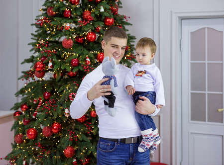 Caucasian young man and his baby son playing with toy mouse at Christmas tree at home Standard-Bild