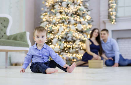 Cute baby sitting on floor and looking at carema. His parents watching him at Christmas tree. Shallow depth of field, boy in focus.