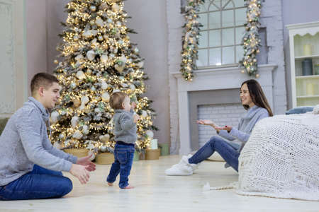 Happy young couple and their baby son near Christmas tree at home. Little boy making first steps.