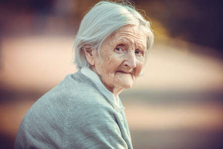 Portrait of senior woman in park looking at camera