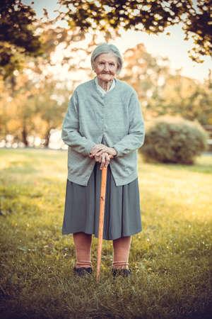 Portrait of senior woman with walking stick in autumn park Standard-Bild