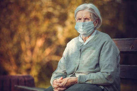 Portrait of senior woman in medical mask sitting on bench in park