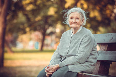 Portrait of senior woman in autumn park looking at camera