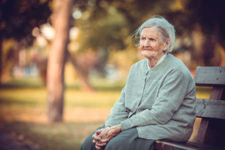 Portrait of senior woman sitting on bench in autumn park. Old lady feeling lonely and sad. Frustrated aged female outdoors.