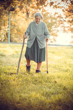Senior woman with canes walking in park on bright autumn day