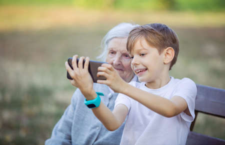 Young boy and his great grandmother using smartphone to take selfie. Making video call. Mobile internet.