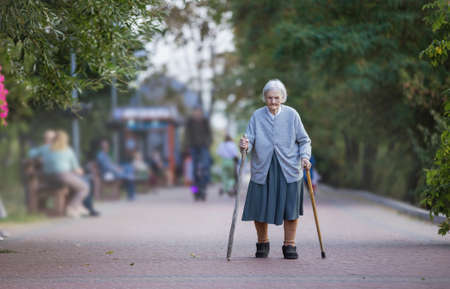 Senior woman with two canes walking in park