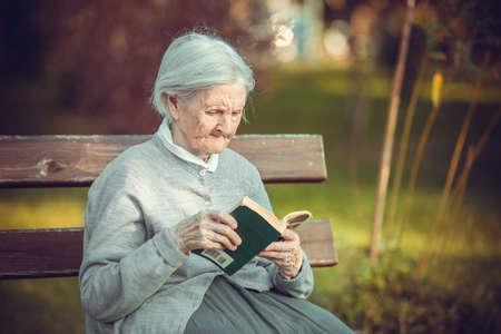 Portrait of senior woman in park reading fiction book