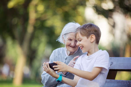 Young boy and his great grandmother using smartphone to makie video call or take selfie. Streaming online video call. Mobile internet. Watching video on smartphone.