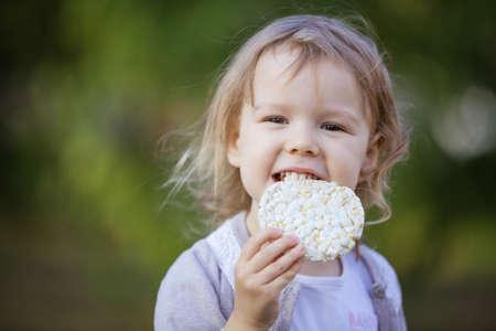 Happy little girl eating corn cracker in summer park