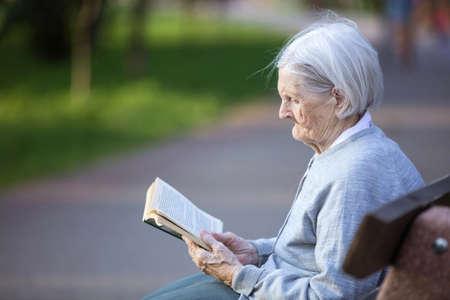 Portrait of senior woman reading fiction book in park Standard-Bild