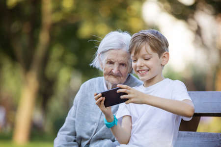 Young boy and his great grandmother using smartphone to take selfie. Making video call. Streaming online video call. Mobile internet. Playing game or watching video on smartphone.