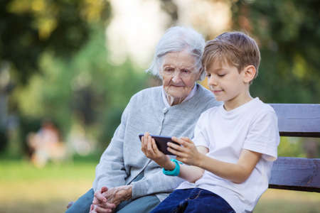 Young boy and his great grandmother watching video on smartphone. Using smartphone to take selfie. Making video call. Mobile internet. Playing game on cellphone. Standard-Bild