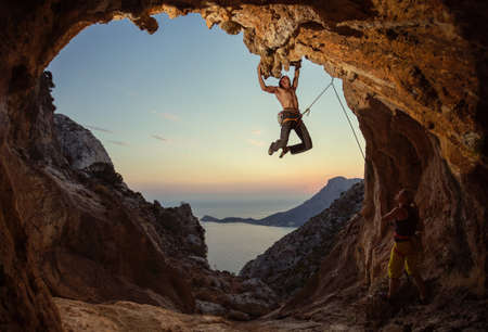 Rock climbing at sunset. Young man climbing route in cave, female partner belaying him. Cave shaped Standard-Bild