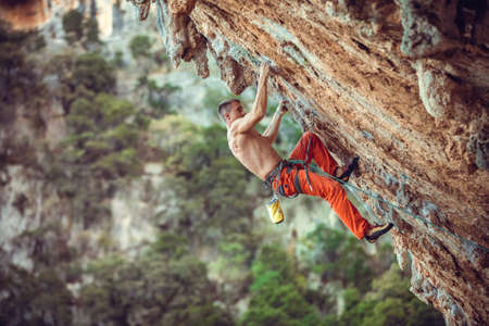 Young male rock climber on overhanging wall. Rock climbing on natural cliff. Strong young man struggling up challenging route. Standard-Bild