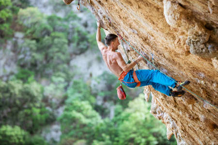 Rock climber on overhanging wall. Rock climbing on natural cliff. Strong young man trying hard to grip small handholds on challenging route. Standard-Bild