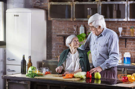 Mature man and his mother cooking together. Senior couple preparing meal in kitchen. Woman is chopping vegetables. Standard-Bild